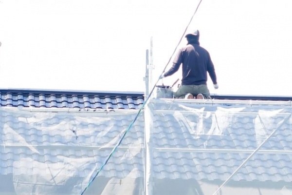 屋根の上にいる業者